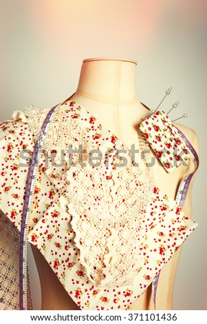 Tailors dummy with colour swatches and lace - stock photo