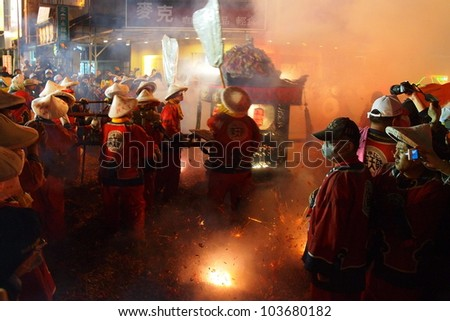 TAIPEI, TAIWAN - DEC 5: The parade of Mazhu (Chinese sea god) in Tainan, Taiwan on December 5, 2011 . It is a custom to set firecracker to welcome the god's sedan chair in a temple fair in Taiwan. - stock photo