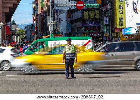TAIPEI, TAIWAN - JUL 16 : A traffic warden stands in the middle of a busy Taipei road directing early rush hour traffic July 16, 2013. Traffic congestion is the top public grievance in Taipei City.