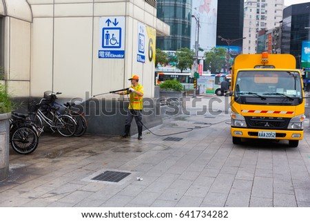 Taipei-Taiwan. May 10, 2016 : Road worker cleaning with atomizer Washing the city street in morning on on Ximending Taipei, Taiwan.