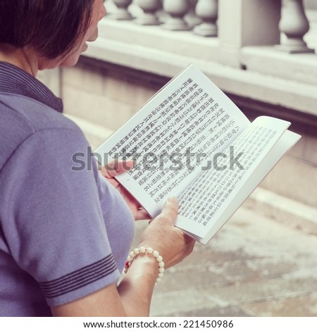 TAIPEI, TAIWAN - MAY 22, 2014: Woman reads from religious song book at Longshan temple in Taipei, Taiwan on May 22, 2014. - stock photo