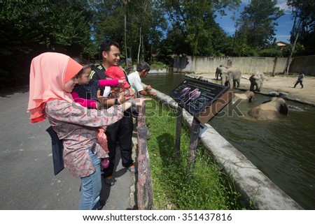 Taiping, Malaysia - 23 March 2015: Tourist enjoy an elephant show in Taiping Zoo. Taiping Zoo is the first animal park in the country. - stock photo