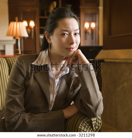 Taiwanese mid adult buisinesswoman looking at viewer with head resting on hand. - stock photo