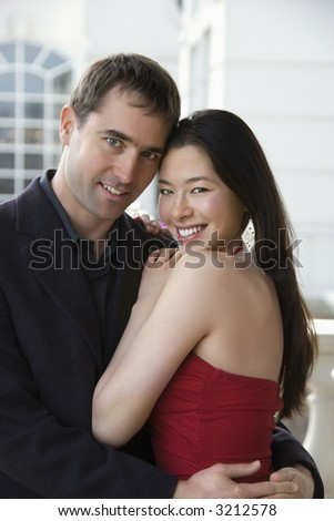 Taiwanese mid adult woman and Caucasian man outdoors embracing and smiling at viewer. - stock photo