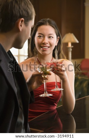 Taiwanese mid adult woman and Caucasian man toasting martinis. - stock photo