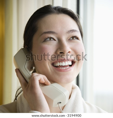 Taiwanese mid adult woman in bathrobe talking on phone and smiling. - stock photo