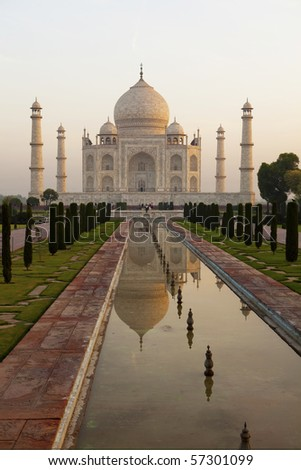 Taj Mahal at sunrise with relection in the pool. - stock photo