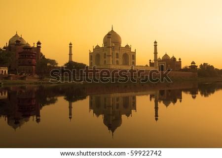 Taj Mahal at sunset reflected in the calm yamuna river. - stock photo
