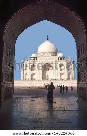 Taj Mahal mausoleum seen from inside mosque at India's Agra. Dark arch with huge doors frames white marble monument against blue skies - stock photo