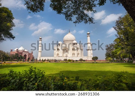 Taj Mahal tomb and green grass at blue cloudy sky in Agra, Uttar Pradesh, India - stock photo
