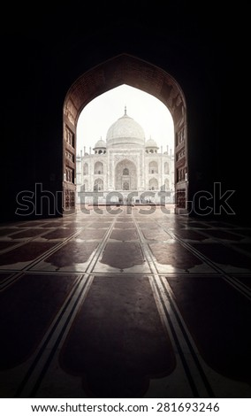 Taj Mahal view in black arch silhouette from the mosque in Agra, Uttar Pradesh, India - stock photo