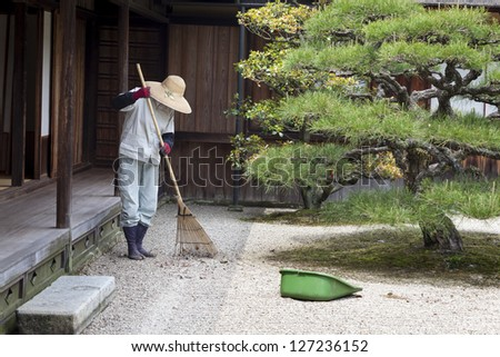 TAKAMATSU, JAPAN - MAY 8 : A gardener rakes the gravel in Ritsurin garden, Takamatsu, Japan on 8th May 2012. Ritsurin is a landscape garden built by the local feudal lords during the early Edo Period.