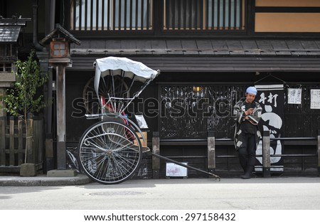 TAKAYAMA, JAPAN - APRIL 12 : Japanese cart with driver in front of a shop in Takayama taken April 12, 2010. Takayama is old town which is register as world heritage site. - stock photo