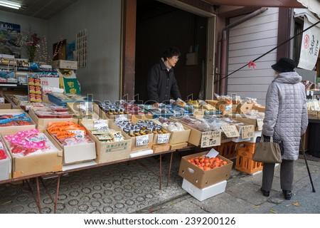 TAKAYAMA, JAPAN - DECEMBER 3, 2014: Local shopping at the Miyagawa morning market in Takayama, Japan. This morning market sells food items, groceries to farm produce and is common in rural Japan. - stock photo