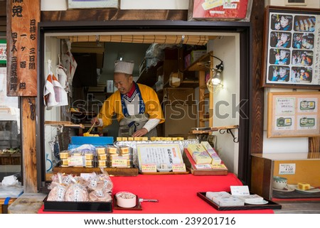 TAKAYAMA, JAPAN - DECEMBER 3, 2014: Vendors at their shop at the Miyagawa morning market in Takayama, Japan. This marketplace sells food items, groceries to farm produce and is common in rural Japan. - stock photo