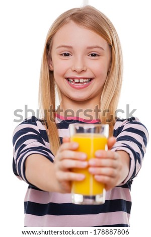 Take a juice! Cheerful little girl stretching out hands with glass of orange juice and smiling at camera while standing isolated on white - stock photo