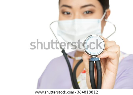 Take a listen. Cropped closeup of a female doctor wearing surgical mask holding stethoscope - stock photo