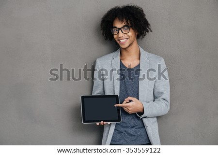 Take a look at this! Cheerful young African man looking at camera with smile and pointing on his digital tablet while standing against grey background - stock photo