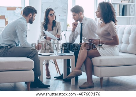 Take a look at this document! Young beautiful woman pointing at document in her hand while sitting on the couch at office with her coworkers  - stock photo