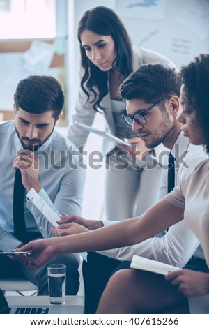 Take a look at this numbers! Young beautiful African woman pointing at her laptop while sitting on the couch at office with her coworkers - stock photo