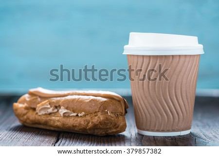 Take away coffe with eclair on wooden background. Copy space for text or advert - stock photo