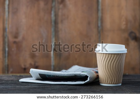 Take away coffee and newspaper on wooden background - stock photo