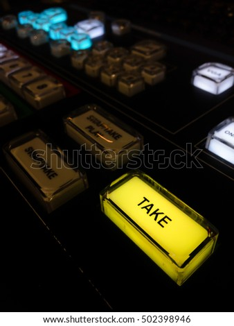 TAKE button on video switcher. Television Broadcast. Dark tone low key.