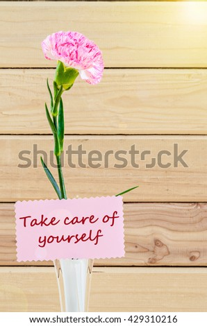 Take care of your self card with Carnation Flowers on White Vase on Wooden Table. - stock photo