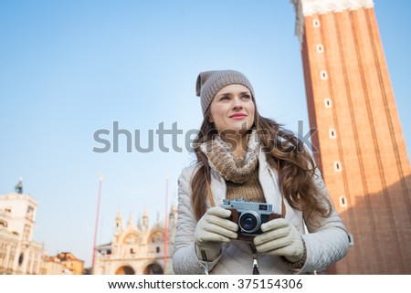 Take classical tourist enjoyment in Venice, Italy - wander over San Marco square, chase pigeons and take photos. Pensive young woman holding retro photo camera in front of Campanile di San Marco - stock photo