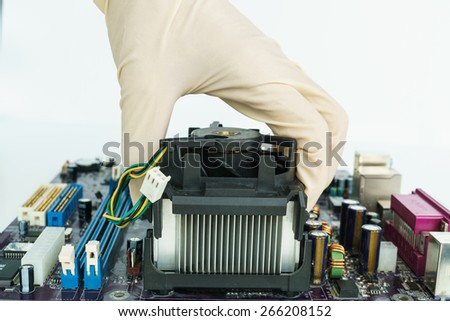take heat-sink by hand on main-board - stock photo