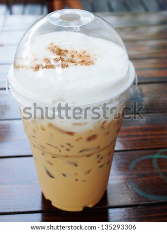 take-home cup of ice coffee on wooden table. - stock photo