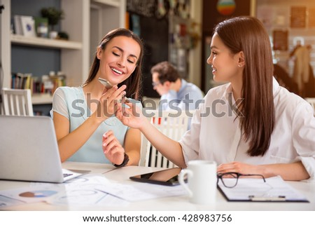 Take it. Overjoyed content charming colleagues holding cell phone and sitting at the table while expressing gladness  - stock photo