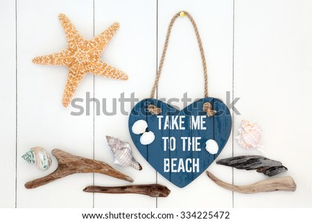 Take me to the beach heart shaped sign with driftwood, starfish and sea shells over white wooden background. - stock photo