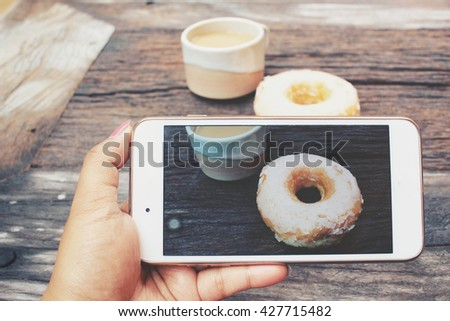 Take photo of donut with smart phone - stock photo
