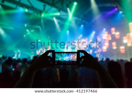 Take photo silhouette crowd in front of concert stage blurred - stock photo