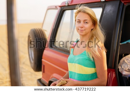Take time to do what makes your soul happy. Shot of young beautiful woman standing near car on the beach.  - stock photo