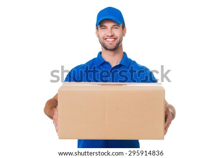Take your package! Happy young courier stretching out a cardboard boxand smiling while standing against white background - stock photo