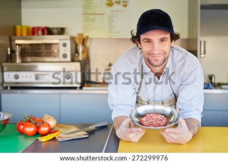Takeaway food entrepeneur standing proudly next to a bowl of fresh high-quality minced red meat with which he makes his hamburger patties - stock photo