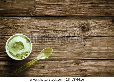 Takeaway tub of creamy green Italian ice cream with a plastic spoon on old rustic wooden boards with plenty of copyspace, overhead view - stock photo