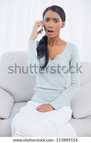 Taken aback attractive woman sitting on cosy sofa in bright living room having a phone call - stock photo