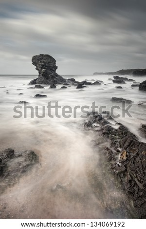 Taken in gale force winds at Porth Y Post on the west coast of Anglesey in North Wales.   Standing above all the turmoil is the lone rock stack which Porth Y Post is famous for.