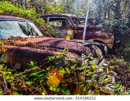 Taken in White, GA, USA on 11/14/15 - A rusty, old, junked car in the woods - stock photo