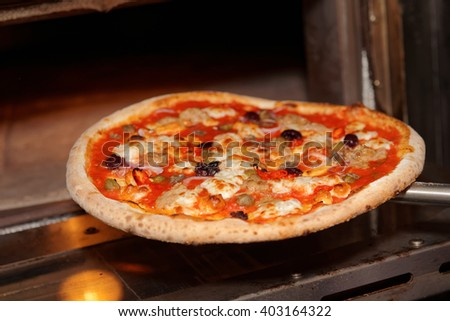 Taking a pizza out of oven, commercial kitchen - stock photo