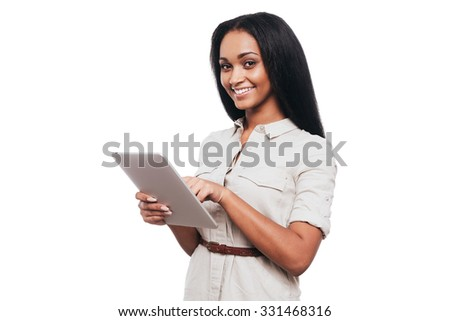 Taking advantages of digital age. Confident young African woman working on digital tablet and smiling while standing against white background - stock photo