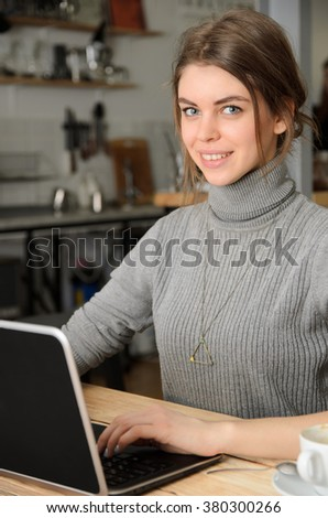 Taking advantages of free Wi-Fi. Beautiful young woman working on laptop