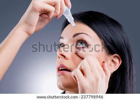 Taking care of her vision. Side view of young women applying eye drops while standing against grey background - stock photo