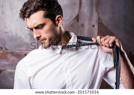 Taking his necktie away. Tired young man in formalwear taking off his necktie and looking away - stock photo