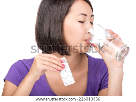 Taking medication. Asian young woman with glass of water takes pills, isolated on white. - stock photo