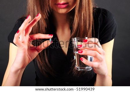 taking medicine with a glass of water - stock photo