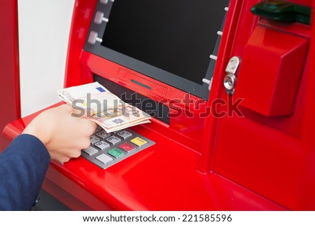 Taking money out of ATM - stock photo
